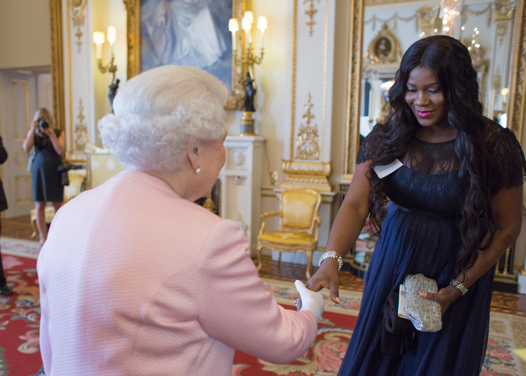 STEPHANIE LINUS AND LINUS IDAHOSA WITH THE QUEEN OF ENGLAND